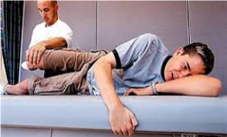 Brian Trzaskos stretching Patrick Irland, Columbine High School shooting victim during physical therapy